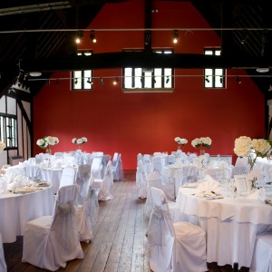 Several round tables covered in white cloths with matching chairs and white flowers. Each with places set for a meal. The half timbered walls and beams above.