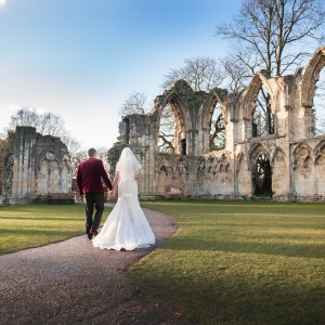 A man and woman dressed in formal wedding attire walk away from the camera across a lawn to medieval ruins
