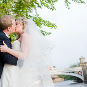Bride and groom kissing next to a river and bridge