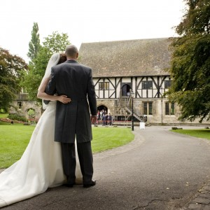 A man and woman in formal wedding attire face away from the camera toward the medieval Hospitium. Lawns and trees are on either side