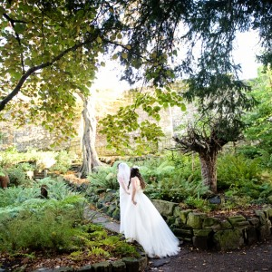 Bride and bridesmaid walk through gardens