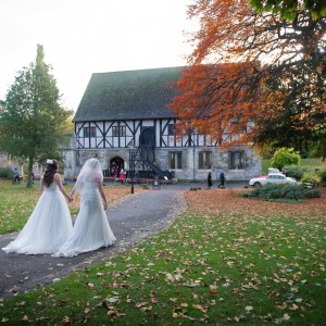 Bride and bridesmaid walk through gardens towards historic building