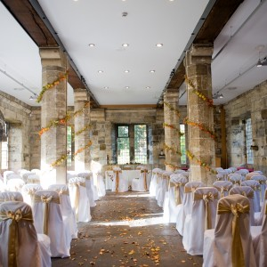 A stone hall with four pillars wrapped in greenery. At the head is a table prepared for a wedding.