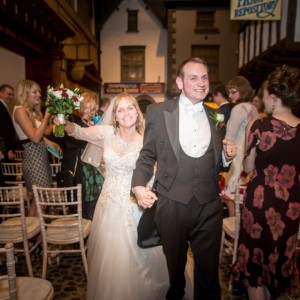 Bride and groom walking down centre aisle in historic venue