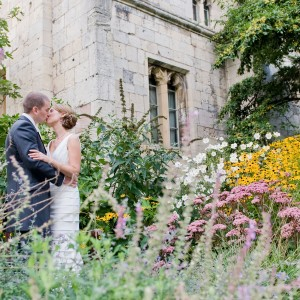 A man and woman in formal wedding attire embrace and kiss in front of a stone building. Spring flowers are all around.