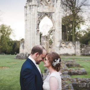 Bride and groom embrace in gardens with abbey ruins