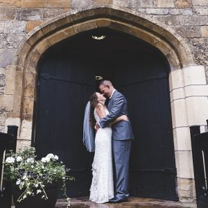 Bride and groom embrace outside historic building