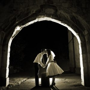 Bride and groom kiss under stone arch at night
