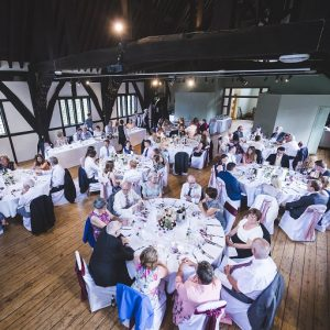 Wedding guests seated at dining tables in a historic building