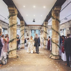 Bride and groom walk down the aisle in historic building