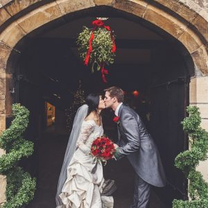 Bride and groom kiss at entrance of historic building