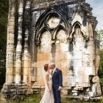 Bride and groom kiss beside abbey ruin